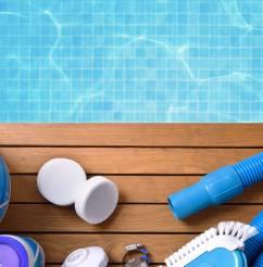 Testeur d'eau, tuyau, galets de chlore... une partie du kit d'entretien de piscine a été posé au bord de la piscine.